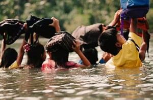 Children wade through the sea to go to school